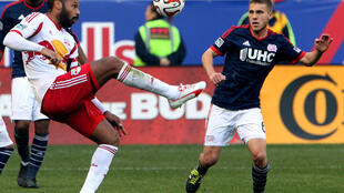 New York Red Bulls forward Thierry Henry kicks the ball away from New England Revolution midfielder, 23 November 2014.