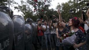 Des manifestants lancent des pétales de fleurs sur les forces de l'ordre, à Erevan, le 23 juin.