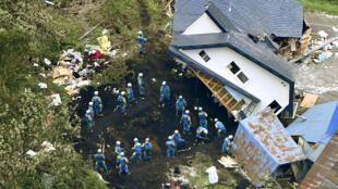 日本警方在遭遇地震后山体滑坡破坏的房屋中寻找幸存者 2018年9月7日