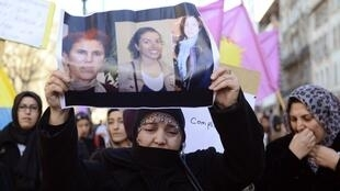 In Marseille, a Kurdish woman holds up pictures of the three PKK members killed the night before in Paris.