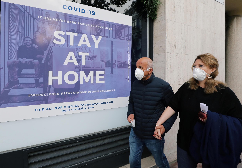 """Прохожие на фоне плаката """"Оставайтесь дома"""" в Ницце. 22 марта 2020 г."""