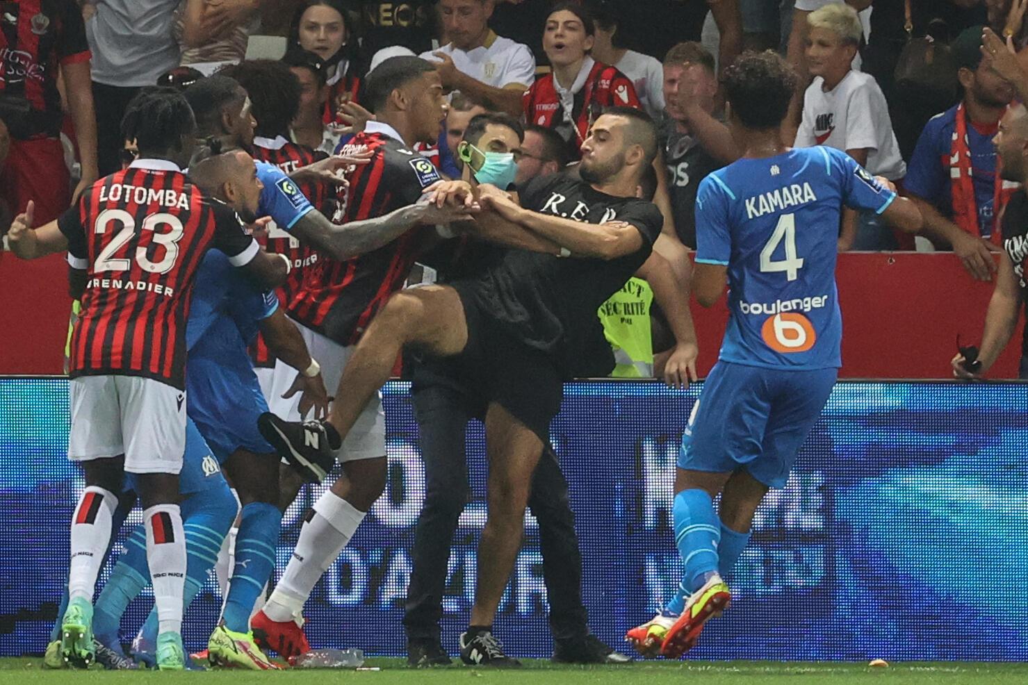 Des joueurs de Nice et de Marseille bloquent un supporter qui tente de donner un coup de pied au joueur marseillais Dimitri Payet (2e g) lors du match de L1 Nice-Marseille interrompu, le 22 août 2021 à Nice