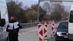 Un officier de police vérifie les papiers d'un conducteur à l'une des sorties de Sofia, après que la ville a été bouclée afin de prévenir la propagation de l'épidémie de Covid-19, le 17 avril 2020.