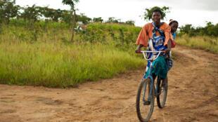 Une femme à vélo revenant du centre de santé avec son enfant. (Photo d'illustration)