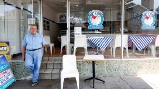 Un employé d'un restaurant de «fish and chip» attend l'arrivée de la pêche à Durban, en Afrique du Sud, le 10 mars 2020.