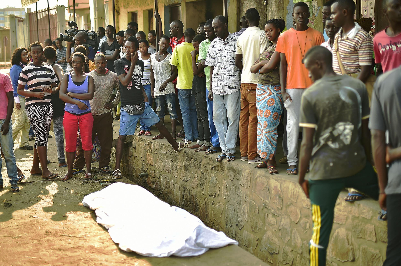 People gather around the body of a man shot dead in the Nyakabiga neighbourhood of Bujumbura, 21 July 21 2015.