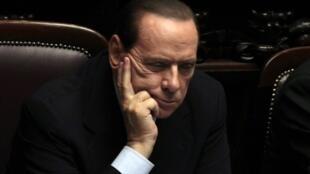 Silvio Berlusconi, clinging on.