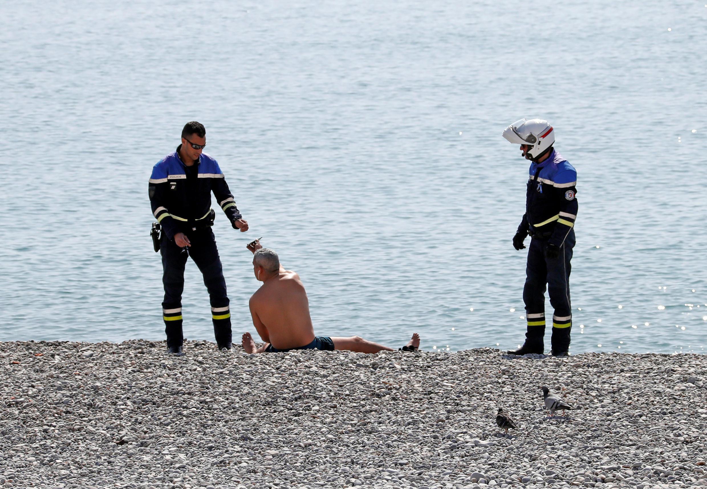 Cảnh sát kiểm tra giấy tờ một người ngoài bãi biển Promenades des Anglais, tại Nice, miền nam nước Pháp ngày 19/3/2020.