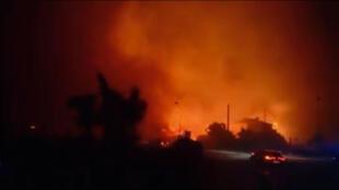 Cars drive past forest fires in Biguglia, near the town of Bastia, Corsica