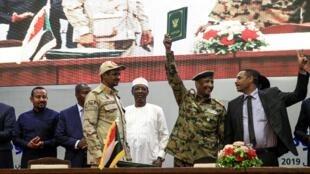 Ahmed al-Rabie, représentant de l'Alliance pour la liberté et le changement (D) et Mohammed Hamdan Daglo, le numéro 2 du Conseil militaire (G en treillis), lors de la signature de l'accord ouvrant la voie à un transfert du pouvoir aux civils, le 17/08/19.