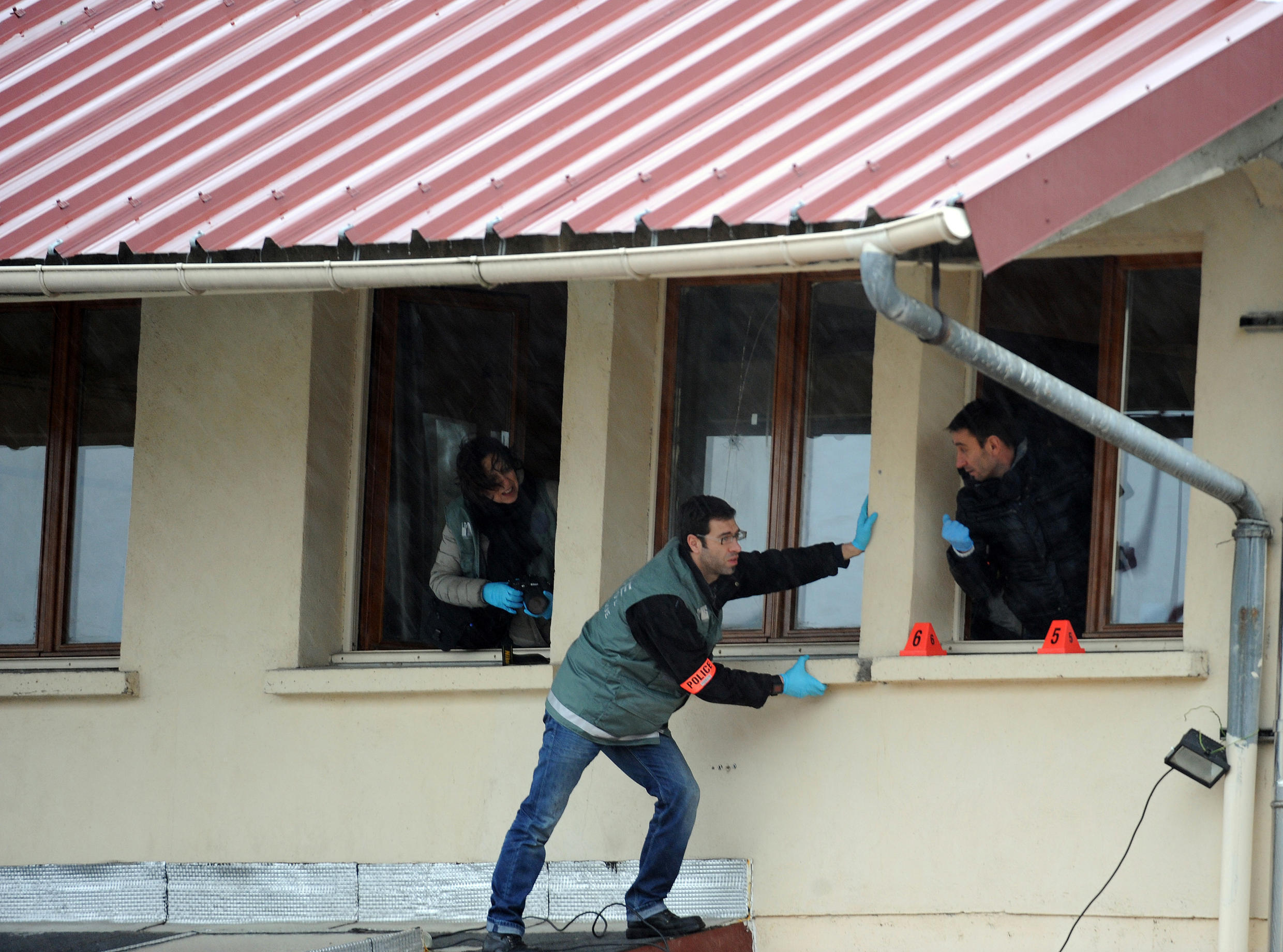 Forensic police examine the scene of an attack on a mosque in Le Mans the day after the murders at Charlie Hebdo's offices