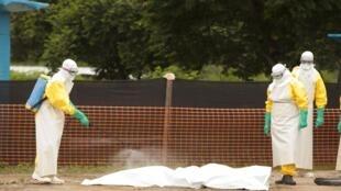 Nhân viên y tế tiệt trùng xác người chết vì Ebola tại Liberia, ngày 30/07/2014.