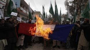 Supporters of religious group Jamaat ahle Hadees burn the French flag at a protest in Quetta on Friday