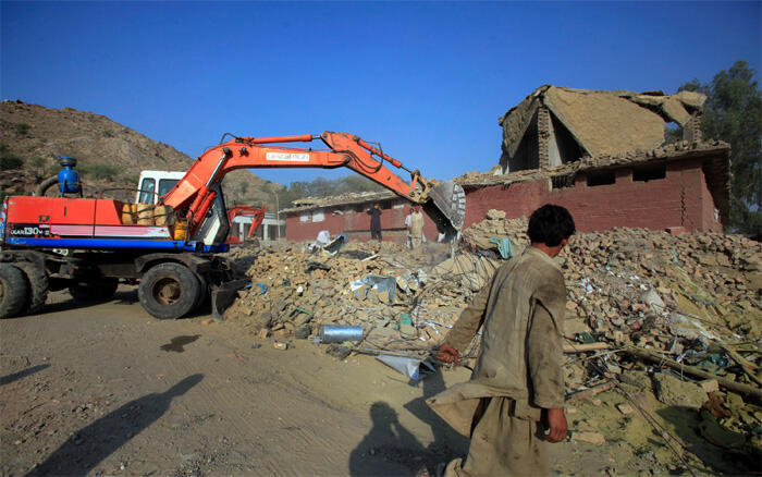 Tractors move rubble from destroyed shops in Pakistan's Mohmand ethnic Pashtun tribal region