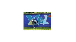 Un réfugié peint le mur de l'ancienne caserne à Munich.