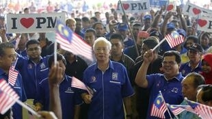 Le Premier ministre, Najib Razak (C), drapeau à la main, chante l'hymne national entouré de ses partisans durant un rassemblement à Rawang, près de Kuala Lumpur, le 28 avril 2013.
