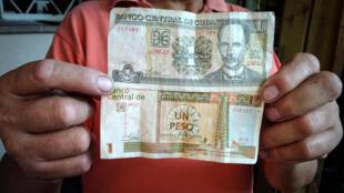 Un ciudadano muestra sendos billetes de las dos monedas que se fusionarán a partir del 1 de enero de 2021 en Cuba