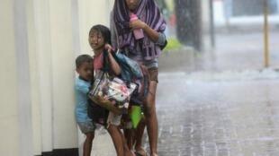 Une mère protège ses enfants, alors que le cyclone Haiyan frappe la ville de Cebu, aux Philippines.