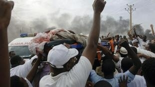Manifestantes carregam corpo de homem morto durante protestos em Cartum, no Sudão