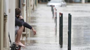 Un homme est assis en face de sa maison dans une rue inondée à Montargis dans le Loiret, à la suite de fortes pluies en France, le 1 juin 2016.