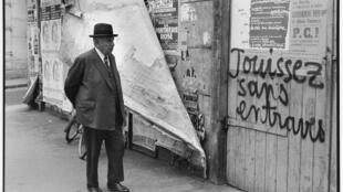 """Um senhor observa um dos célebres slogans de Maio de 68 na França: """"Jouissez sans entraves"""", """"Gozem sem impedimentos"""", diz a frase, que simbolizava o desejo de liberação dos estudantes."""