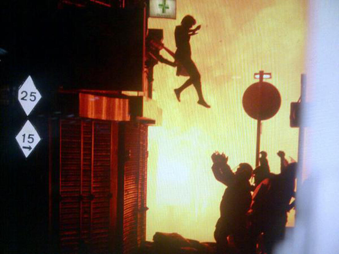 A woman leaps from a building in flames in London