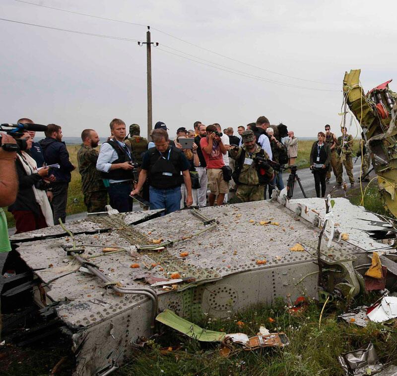 Des inspecteurs de l'OSCE, accompagnés de miliciens séparatistes ukrainiens pro-russes, autour des débris du vol MH17 de la Malaysian Airlines à Grabovo dans la région de Donetsk, le 18 juillet 2014.