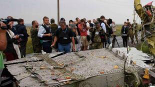 Des inspecteurs de l'OSCE, accompagnés  des miliciens séparatistes ukrainiens pro-russes, inspectent les débris du vol MH17 de la Malaysia Airlines à Grabovo dans la région de Donetsk, le 18 juillet 2014.