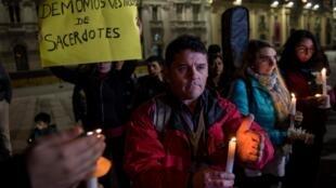 Un manifestant brandit une pancarte où on peut lire «des démons en habits de prêtres», lors d'une manifestation contre les scandales d'abus sexuels, à Santiago du Chili, le 20 août 2018.