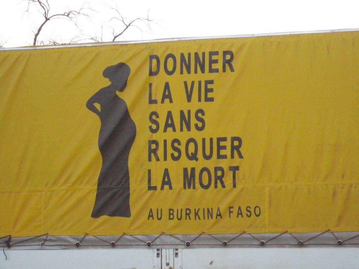 """Một khẩu hiệu cổ vũ cho việc cải thiện sức khỏe thai phụ tại Châu Phi : """"Để cho người đem lại sự sống không bị thần chết đe dọa""""."""