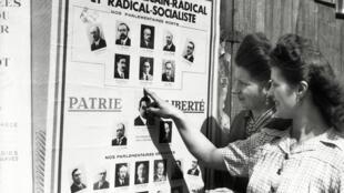 Em Paris, duas mulheres olham o cartaz do partido de esquerda, antes de votar pela primeira vez.