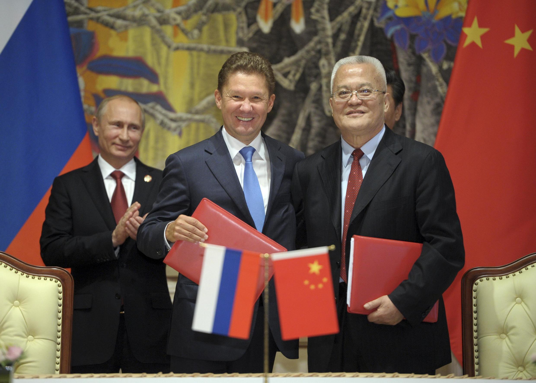 Le PDG de Gazprom Alexei Miller (c.), le président du consortium national chinois du pétrole Zhou Jiping  (d.) et le président de la Russie Vladimir Poutine (g.) lors de la signature d'un contrat gazier, à Shangai le 21 mai 2014.