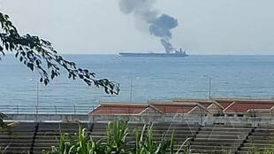 A handout picture released by the official Syrian Arab News Agency (SANA) on April 24, 2021  shows smoke billowing from a tanker off the coast of the western Syrian city of Banias