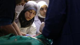 A médica Amani Ballour (centro) na cabeceira de feridos recolhidos ao hospital suterrâneo que ela dirigiu na região rebelde de Goutha, na Síria.