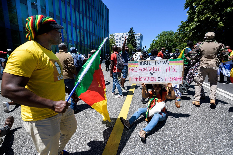 Une femme porte une banderole avec l'inscription «Paul Biya, premier responsable de l'immigration en Europe» lors d'une manifestation contre la présence du président camerounais Paul Biya à Genève, le 29 juin 2019.