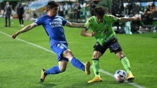 Un jugador del Jeonbuk Hyundai Motors trata de proteger el balón ante la llegada de un rival del Suwon Samsung Bluewings durante un partido de la liga surcoreana de fútbol, el 8 de mayo de 2020 en el estadio de Jeonju (Corea del Sur)