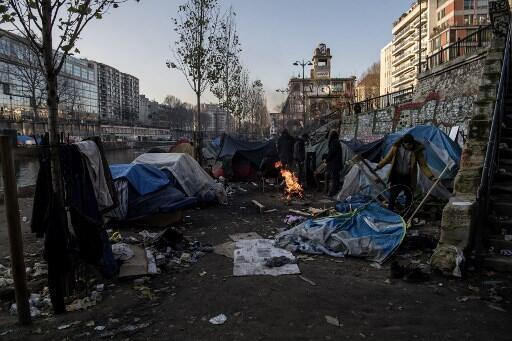Migrants, mainly from Afghanistan, warm themselves up around a bonfire as freezing temperatures settle along the canal Saint-Martin in Paris.