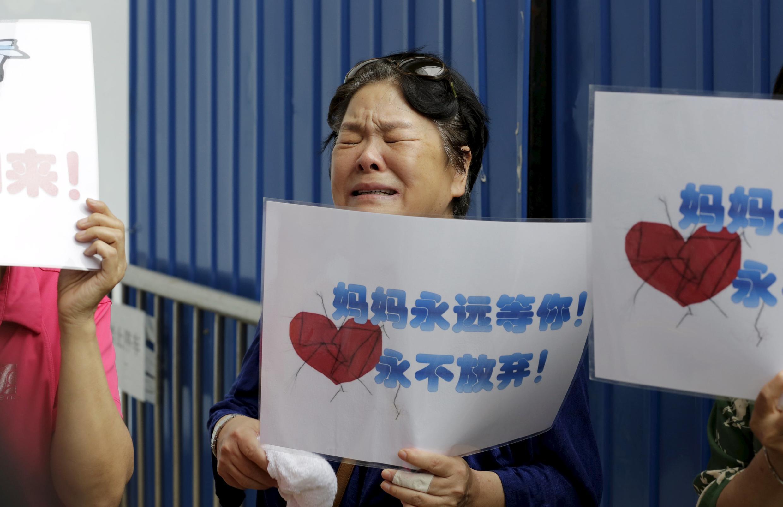 Familles chinoises des disparus du vol MH370 de Malaysia Airlines éplorées devant le siège de la compagnie à Pékin ce jeudi 6 août 2015.