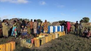 Les habitants de Nikoly, l'un des villages bénéficiaires du pipeline d'eau potable, patientent pour pouvoir remplir leur bidon de 20 litres.