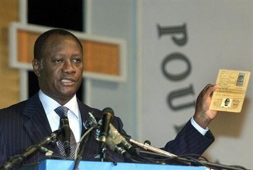 Alassane Ouattara montre sa carte d'identité prouvant sa nationalité ivoirienne lors du Forum national de la réconciliation à Abidjan le 1er décembre 2000.