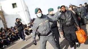 Imigrantes tunisianos presos pela polícia no momento de seu desembarque na ilha de Lampedusa, na Itália, no dia 30 de março de 2011.