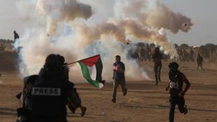 Des manifestants palestiniens fuient entre les gaz lacrymogènes tirés par les troupes israéliennes lors d'une manifestation marquant le 70e anniversaire de la Nakba, à la frontière entre Israël et Gaza, dans le sud de la bande de Gaza, le 15 mai 2018.
