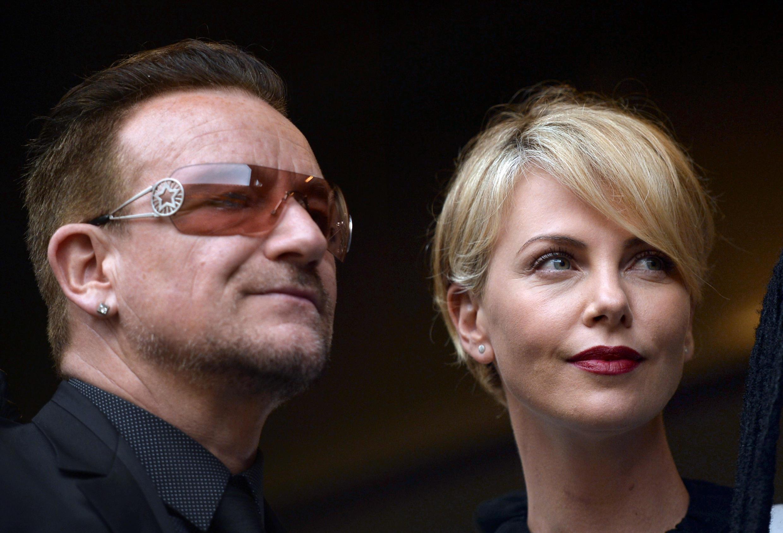 Bono, l'ancien chanteur des U2 et l'actrice sud-africaine Charlize Theron pendant la cérémonie d'hommage à Nelson Mandela au stade de Soccer city à Johannesbourg, le 10 décembre 2013.
