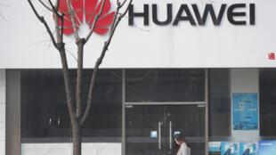ស្ត្រីម្នាក់ដើរកាត់ហាងលក់ទូរស័ព្ទដៃ Huawei មួយកន្លែង នៅក្នុងទីក្រុងប៉េកាំង ប្រទេសចិន កាលពីថ្ងៃទី ២ មីនា ឆ្នាំ២០១៩។