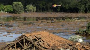 (法广存档图片) Image d'archive RFI : Le géant minier brésilien Vale a signé un accord de conciliation le jeudi 4 février 2021 pour verser 37,7 milliards de reais (7 milliards de dollars) à l'État de Minas Gerais, à la suite de l'effondrement d'un barrage il y a deux ans qui a dévasté la ville de Brumadinho et tué. au moins 272 personnes. Le 27 janvier 2019, des secouristes dans un hélicoptère fouillent une zone inondée après l'effondrement d'une digue à Brumadinho, au Brésil.