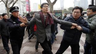 Một thanh niên bi công an bắt giữ trước rạp hát Hòa Bình tại Thượng Hải (Trung Quốc). Đây là một điểm tập hợp của những người được kêu gọi biểu tình ngày 20/02/2011 để ủng hộ cuộc Cách mạng Hoa nhài.