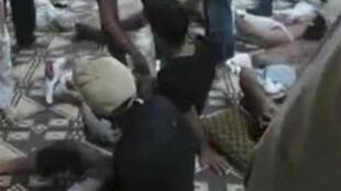 Reprodução de vídeo com imagem de corpos de vítimas de tropas do goevrno sírio em Hama.