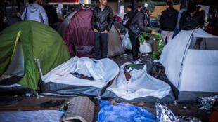 Des migrants se tiennent entre les tentes dans un camp de fortune au boulevard de la Villette, près des stations de métro Jaurès et Stalingrad, dans le nord de Paris, le 31 octobre 2016.