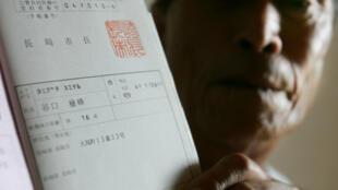 Em foto de arquivo de 2005, Taniguchi mostra cartão de sobrevivente da bomba de Nagasaki.