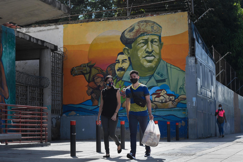 Moradores de Caracas passam diante de mural com rostos do ex-presidente Hugo Chávez e do presidente Nicolás Maduro. 28 de julho de 2020.